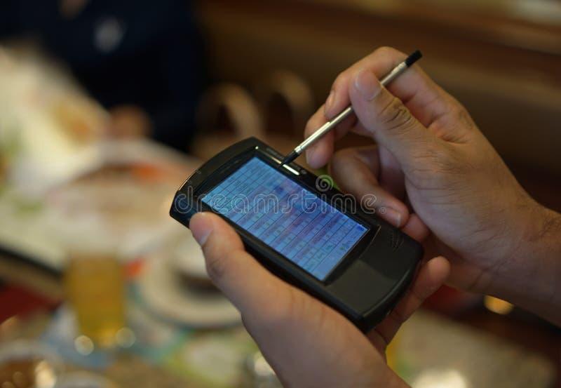 Ένας σερβιτόρος που χρησιμοποιεί μια τσέπη PC, τεχνολογία PDA στοκ φωτογραφίες