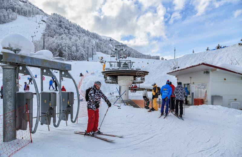 Ένας σκιέρ έχει περάσει μια περιστροφική πύλη για την τροφή επάνω σε έναν ανελκυστήρα καρεκλών στο χιονοδρομικό κέντρο χειμερινών στοκ εικόνα με δικαίωμα ελεύθερης χρήσης