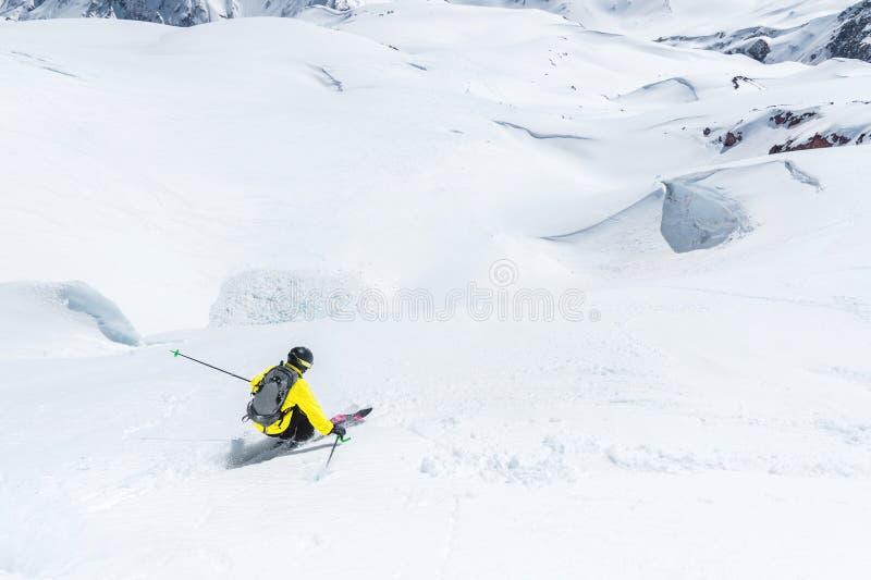 Ένας σκιέρ με την ταχύτητα οδηγά σε ένα χιονώδες freeride κλίσεων Η έννοια του χειμερινού ακραίου αθλητισμού στοκ φωτογραφίες