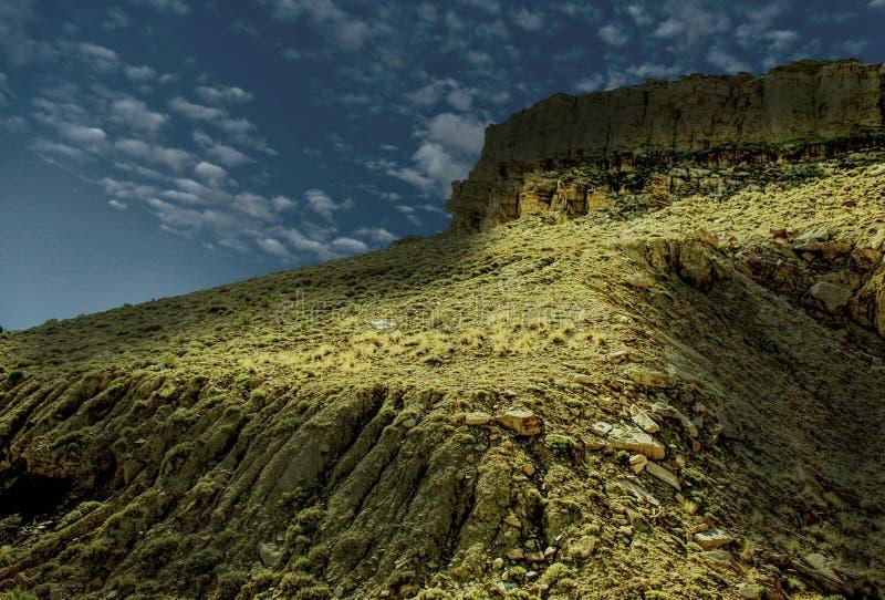 Ένας σκιασμένος απότομος βράχος ενάντια σε έναν σκούρο μπλε ουρανό στοκ εικόνα