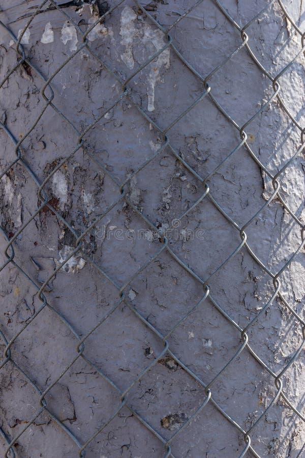 Ένας σκουριασμένος φράκτης σιδήρου με το χρώμα αποφλοίωσης στο υπόβαθρο του σπιτιού στοκ φωτογραφία