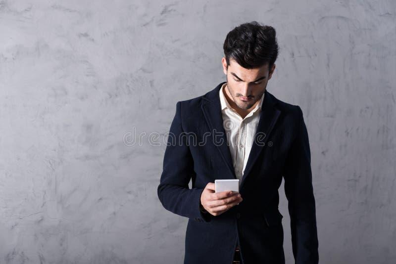 Ένας σοβαρός νέος επιχειρηματίας που χρησιμοποιεί ένα smartphone στοκ φωτογραφίες με δικαίωμα ελεύθερης χρήσης