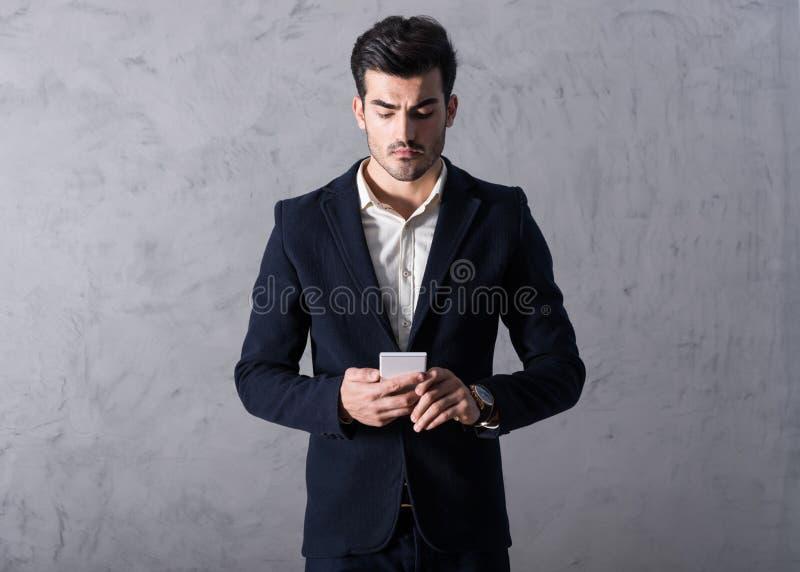 Ένας σοβαρός νέος επιχειρηματίας που χρησιμοποιεί ένα smartphone στοκ φωτογραφίες