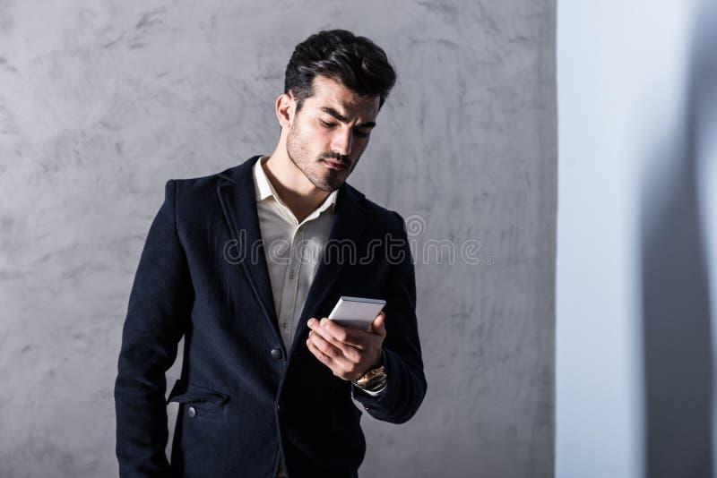 Ένας σοβαρός νέος επιχειρηματίας που χρησιμοποιεί ένα smartphone στοκ εικόνα με δικαίωμα ελεύθερης χρήσης