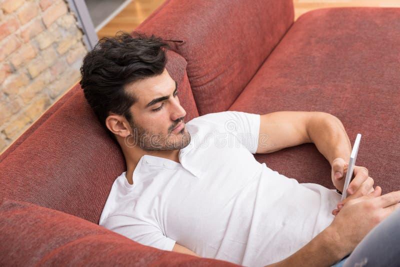 Ένας σοβαρός νεαρός άνδρας που βάζει σε έναν καναπέ και που χρησιμοποιεί το smartphone του στοκ εικόνες