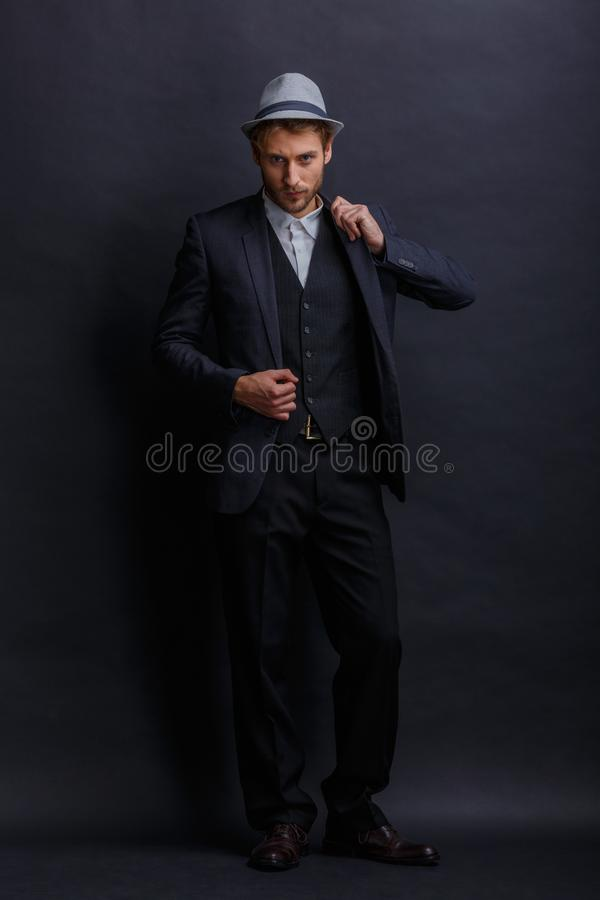 Ένας σοβαρός νεαρός άνδρας σε ένα κοστούμι και ένα καπέλο, στέκεται και ρυθμίζει το σακάκι του σε τον στοκ εικόνες