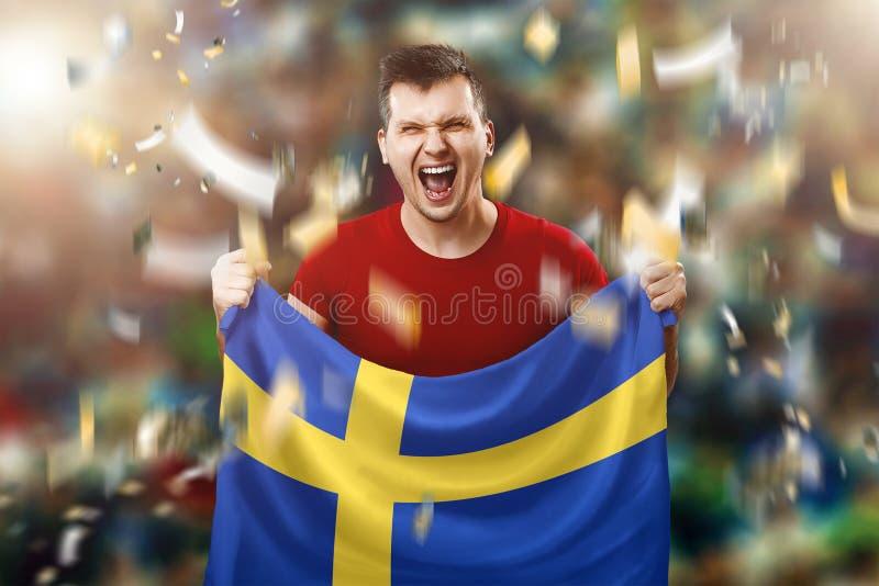 Ένας σουηδικός ανεμιστήρας, ένας ανεμιστήρας ενός ατόμου που κρατά τη εθνική σημαία της Σουηδίας στα χέρια του Ανεμιστήρας ποδοσφ στοκ εικόνες