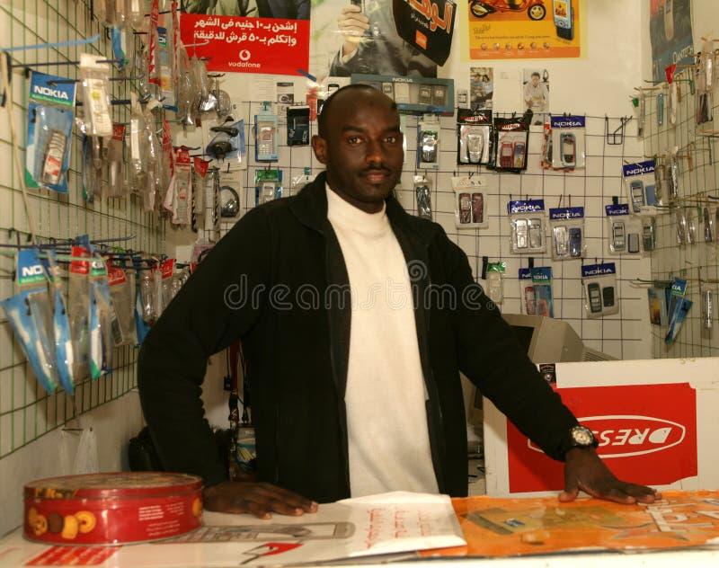 Ένας σουδανέζικος πρόσφυγας στο κινητό τηλεφωνικό κατάστημά του στοκ φωτογραφίες