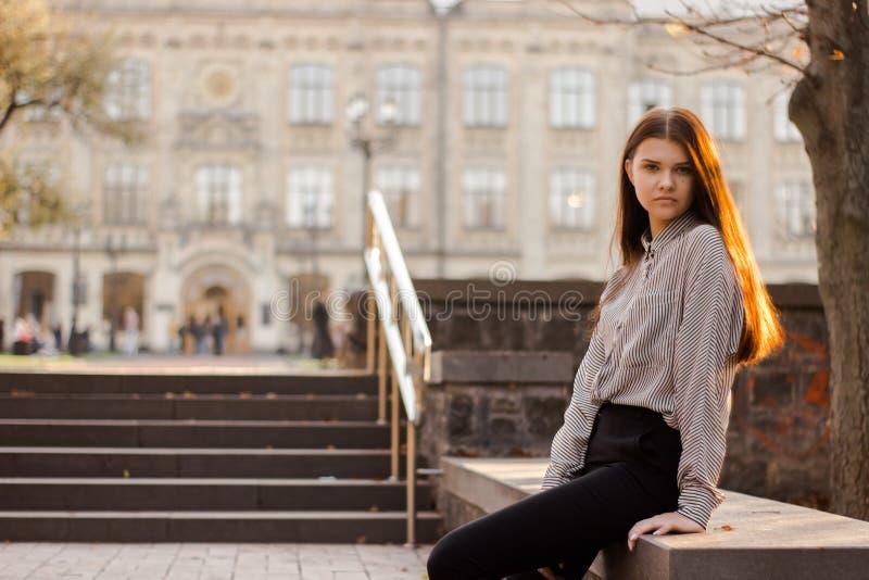 Ένας σπουδαστής κάθεται κοντά στα βήματα που οδηγούν στο πανεπιστήμιο στοκ εικόνες