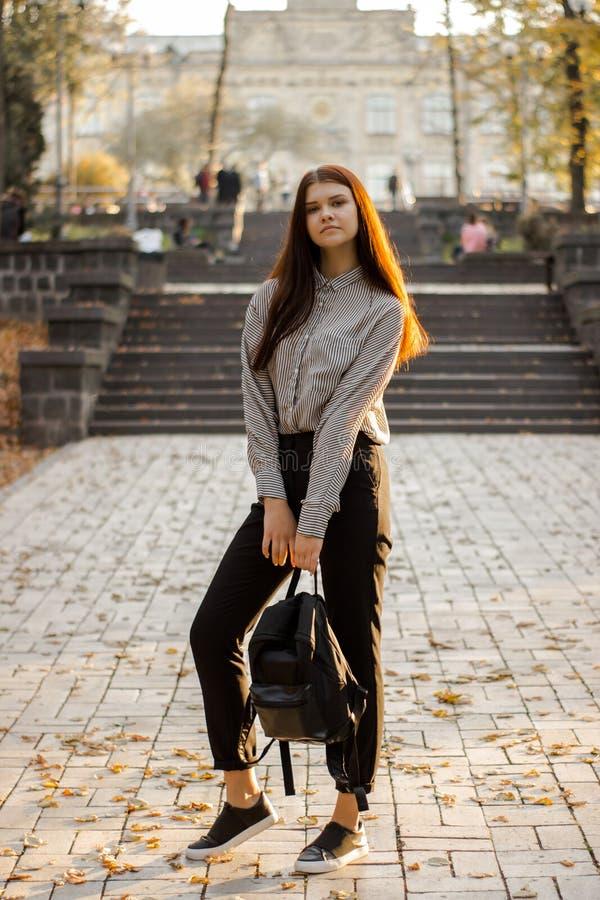 Ένας σπουδαστής με ένα σακίδιο πλάτης στέκεται κοντά στα βήματα που οδηγούν στο πανεπιστήμιο στοκ φωτογραφία με δικαίωμα ελεύθερης χρήσης