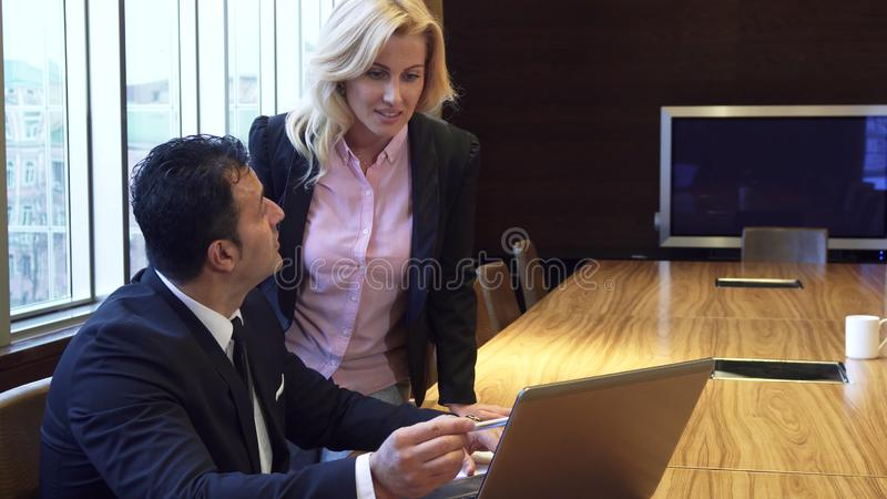 Ένας συγκεντρωμένοι άνδρας και μια γυναίκα που προσέχουν το πρόγραμμά τους για ένα lap-top και που συζητούν το στοκ εικόνα