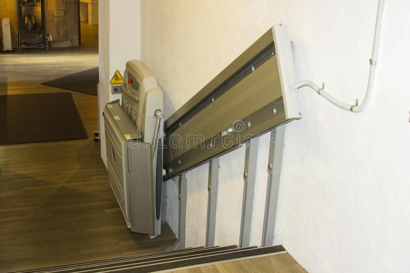 Ένας συμπαγής assistive ανελκυστήρας σκαλοπατιών υποστήριξης σε μια σύντομη πτήση των σκαλοπατιών σε ένα δημόσιο κτίριο στη Βόρει στοκ εικόνες