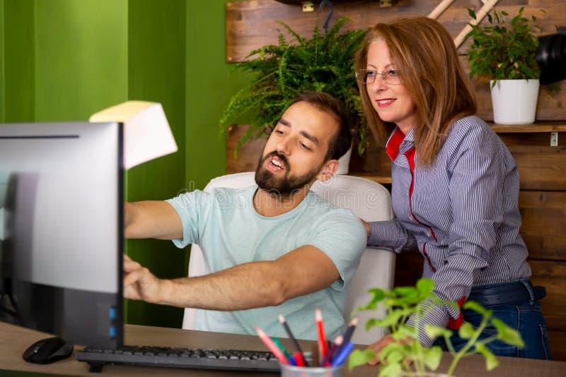 Ένας συνάδελφος λέει κάτι στο αφεντικό στον υπολογιστή στοκ φωτογραφία με δικαίωμα ελεύθερης χρήσης