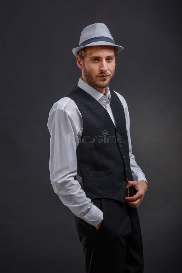 Ένας συνεργάτης πονηριών, σε ένα αναδρομικό κοστούμι και ένα καπέλο, στέκεται με ένα ακλόνητο βλέμμα στοκ εικόνα με δικαίωμα ελεύθερης χρήσης