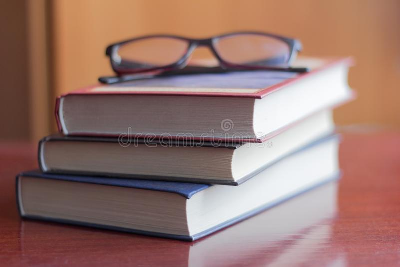 Ένας σωρός διάφορων βιβλίων και γυαλιών στον πίνακα στοκ φωτογραφία με δικαίωμα ελεύθερης χρήσης