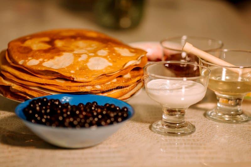 Ένας σωρός του λεπτού ρωσικού καυτού blini τηγανιτών με τις σταφίδες, το μέλι, την ξινές κρέμα και τη μαρμελάδα στοκ εικόνες