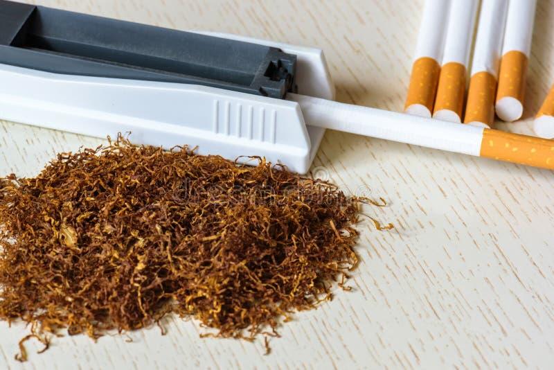 Ένας σωρός του φυσικού καπνού σε έναν άσπρο ξύλινο πίνακα και μια συσκευή για τη χειρωνακτική παραγωγή τσιγάρων Κάπνισμα στοκ εικόνα