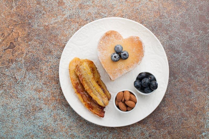 Ένας σωρός των εύγευστων τηγανιτών με το μέλι, τον καφέ και τα βακκίνια στο α σε ένα σκουριασμένο κόκκινο υπόβαθρο Μεγάλο πρόγευμ στοκ εικόνα