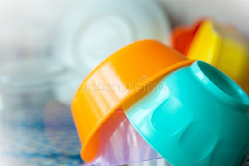 Ένας σωρός των ζωηρόχρωμων πλαστικών κύπελλων στο ράφι στοκ εικόνα