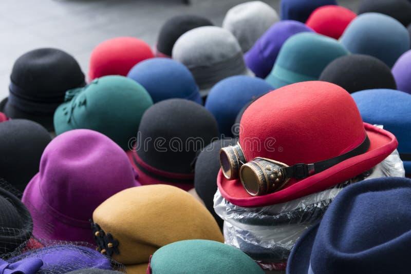 Ένας σωρός των πολύχρωμων καπέλων σφαιριστών σε έναν στάβλο στοκ εικόνες