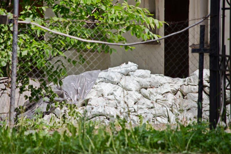 Ένας σωρός των σάκων κατασκευής πίσω από το φράκτη και τη χλόη στοκ φωτογραφία