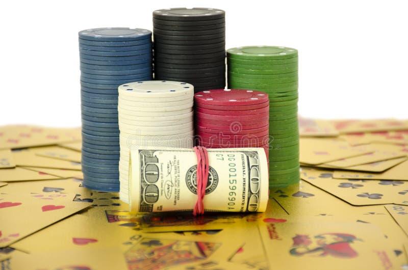 Ένας σωρός των τσιπ μένει στις χρυσές κάρτες με το ρόλο των δολαρίων που απομονώνονται στο υπόβαθρο whitte στοκ φωτογραφία με δικαίωμα ελεύθερης χρήσης
