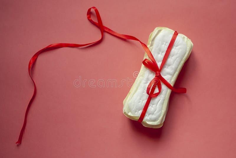 Ένας σωρός των υγειονομικών μαξιλαριών ή των θηλυκών μαξιλαριών υγιεινής έδεσε με μια κόκκινη κορδέλλα σε ένα ρόδινο υπόβαθρο Κρί στοκ φωτογραφία με δικαίωμα ελεύθερης χρήσης