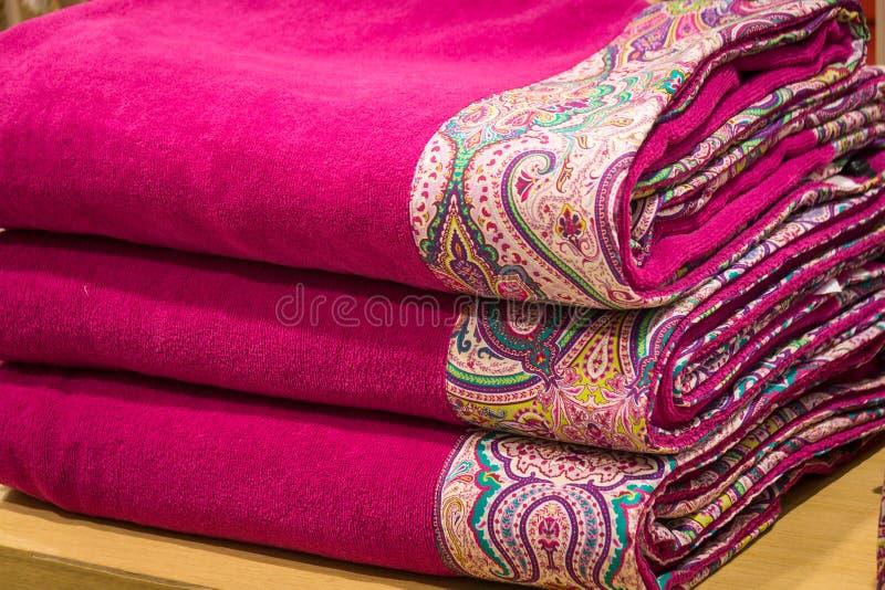 Ένας σωρός των φωτεινών πετσετών με τις αρχικές διακοσμήσεις textile Εξαρτήματα λουτρών στοκ φωτογραφίες