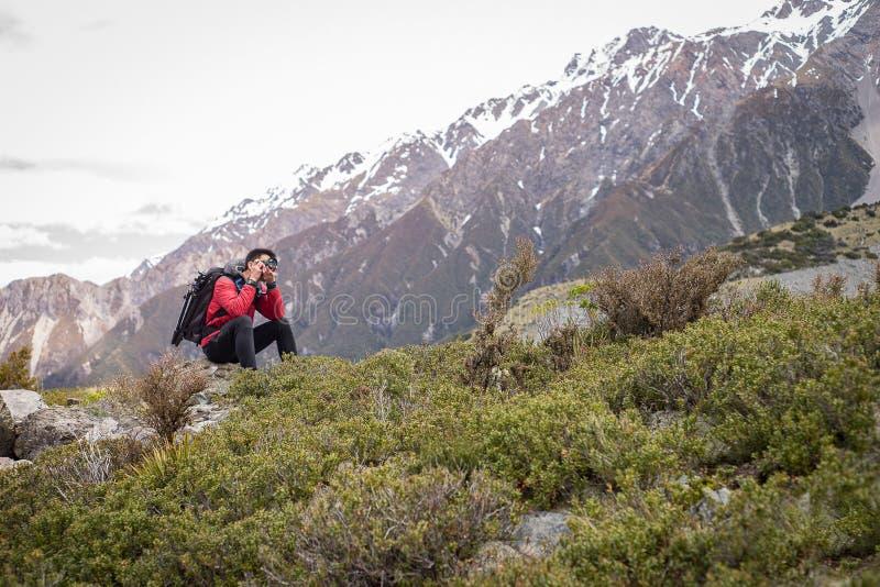 Ένας ταξιδιώτης, άτομο φωτογράφων που παίρνει τη φωτογραφία στο βουνό, χιόνι στοκ φωτογραφίες