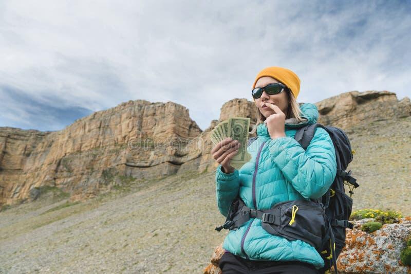 Ένας ταξιδιώτης κοριτσιών στα γυαλιά ηλίου και με ένα σακίδιο πλάτης στο υπόβαθρο των βράχων υψηλών βουνών κρατά σκεπτικά ενός στοκ εικόνα