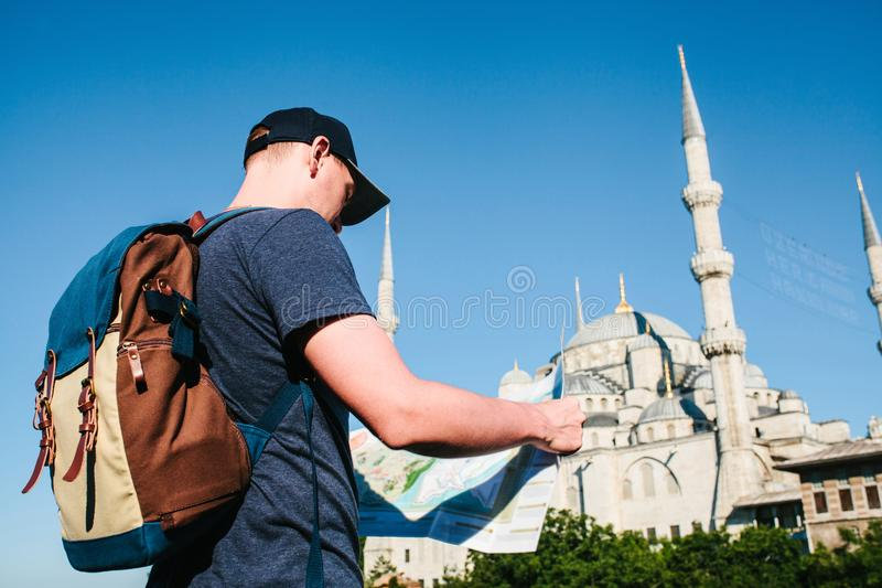 Ένας ταξιδιώτης σε ένα καπέλο του μπέιζμπολ με ένα σακίδιο πλάτης εξετάζει το χάρτη δίπλα στο μπλε μουσουλμανικό τέμενος - η διάσ στοκ φωτογραφίες