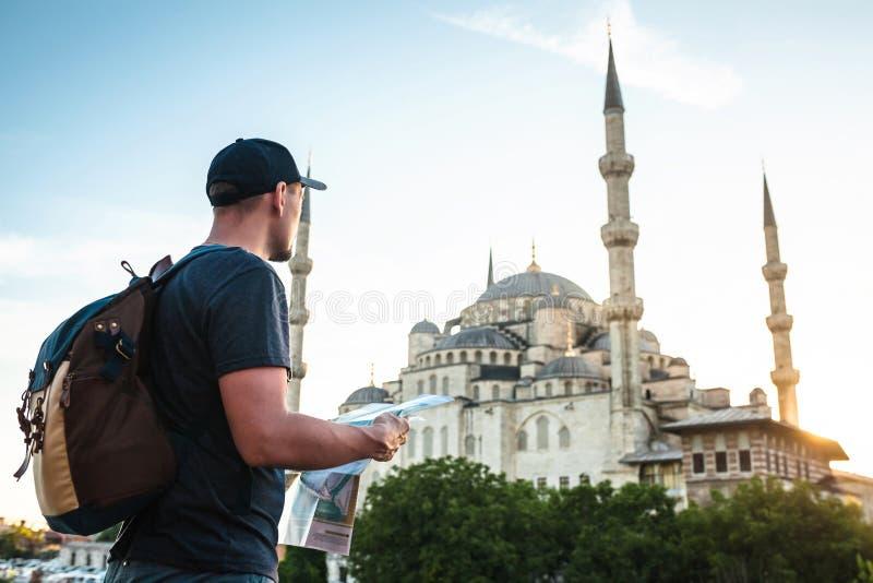 Ένας ταξιδιώτης σε ένα καπέλο του μπέιζμπολ με ένα σακίδιο πλάτης εξετάζει το χάρτη δίπλα στο μπλε μουσουλμανικό τέμενος - η διάσ στοκ εικόνα