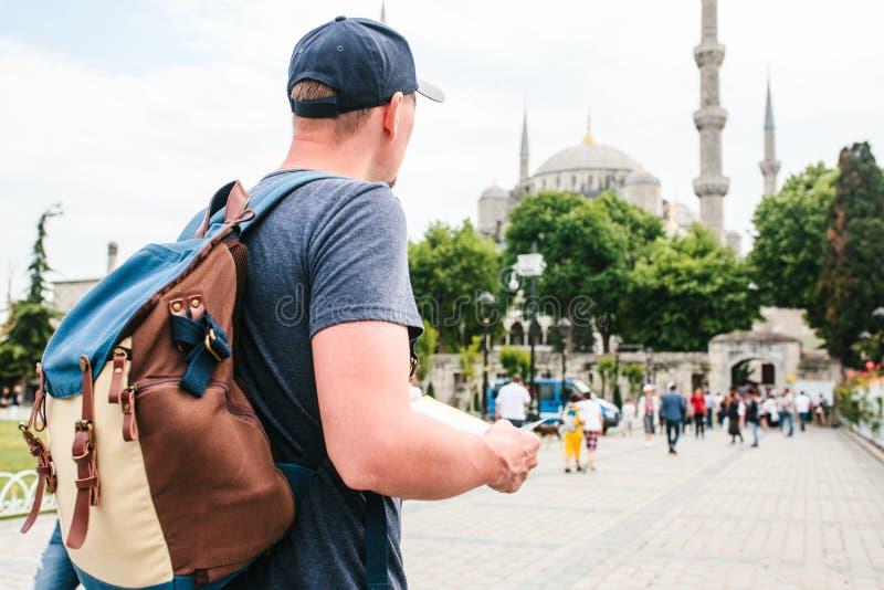 Ένας ταξιδιώτης σε ένα καπέλο του μπέιζμπολ με ένα σακίδιο πλάτης εξετάζει το χάρτη δίπλα στο μπλε μουσουλμανικό τέμενος - η διάσ στοκ εικόνες