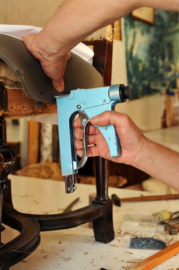 Ένας ταπετσιέρης που επισκευάζει μια πολυθρόνα με stapler στοκ εικόνα με δικαίωμα ελεύθερης χρήσης