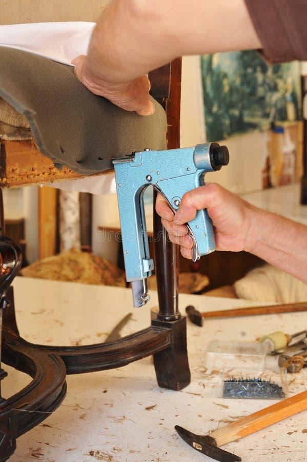 Ένας ταπετσιέρης που επισκευάζει μια πολυθρόνα με stapler στοκ φωτογραφία με δικαίωμα ελεύθερης χρήσης