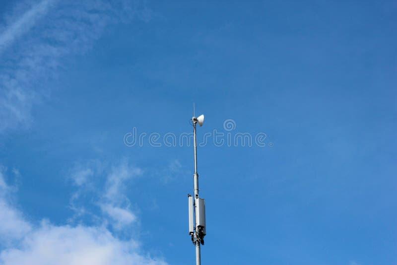 Ένας τηλεφωνικός πύργος κυττάρων στο υπόβαθρο μπλε ουρανού στοκ φωτογραφία