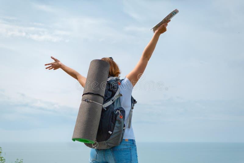 Ένας τουρίστας γυναικών απολαμβάνει τους πραγματοποιημένους στόχους και την όμορφη θέα στοκ εικόνα