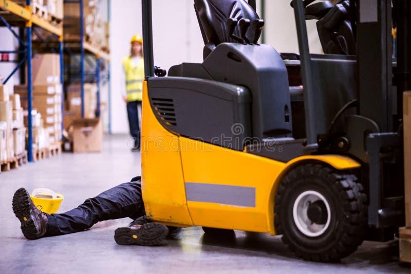 Ένας τραυματισμένος εργαζόμενος μετά από ένα ατύχημα σε μια αποθήκη εμπορευμάτων στοκ εικόνες