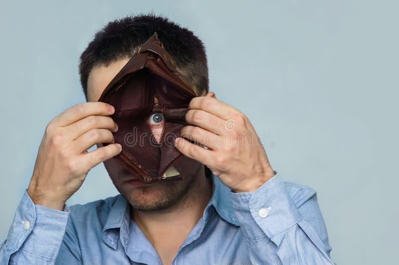 Ένας τύπος κοιτάζει μέσω μιας τρύπας στο κατώτατο σημείο ενός κενού πορτοφολιού δέρματος με την παρουσίαση των αρνητικών συγκινήσ στοκ φωτογραφίες