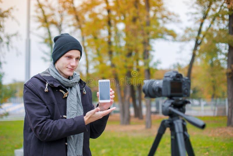 Ένας τύπος παίρνει τις εικόνες του σε μια κάμερα σε ένα τρίποδο που επιδεικνύει ένα κινητό τηλέφωνο υπαίθρια στοκ φωτογραφία