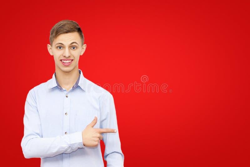 Ένας τύπος που δείχνει ένα δάχτυλο σε μια διαφήμιση, που απομονώνεται σε ένα κόκκινο υπόβαθρο, ένα άτομο διαφημίζει ένα προϊόν στοκ εικόνα με δικαίωμα ελεύθερης χρήσης