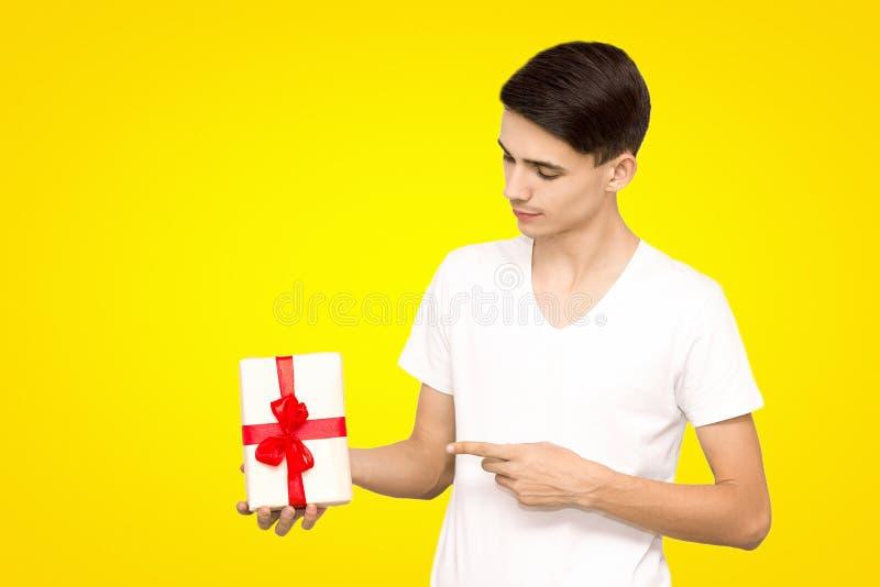Ένας τύπος σε μια άσπρη μπλούζα με ένα δώρο σε ένα κίτρινο υπόβαθρο στο στούντιο στοκ φωτογραφία