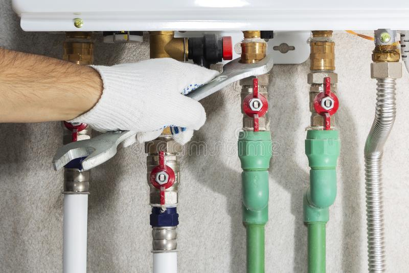 Ένας υδραυλικός συνδέεται με έναν λέβητα σωλήνων αερίου με ένα γαλλικό κλειδί στοκ φωτογραφία