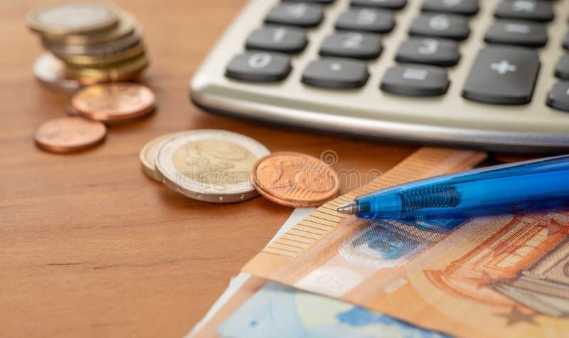 Ένας υπολογιστής με τους ευρο- λογαριασμούς και τους σωρούς νομισμάτων στοκ εικόνες