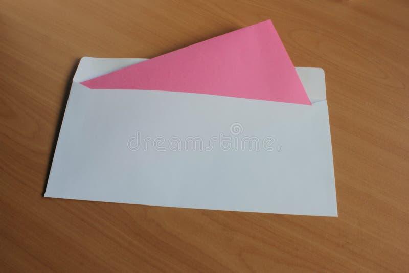 Ένας φάκελος με μια κόκκινη κάρτα είναι στον πίνακα στοκ φωτογραφίες