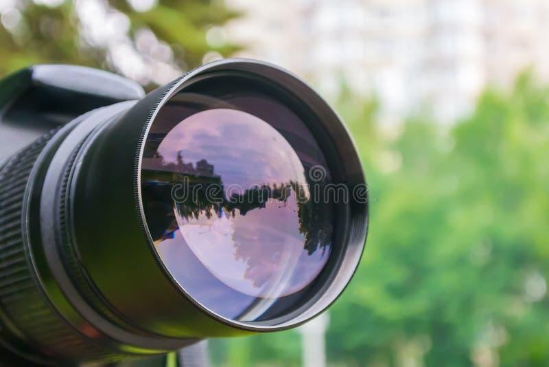 Ένας φακός καμερών κινηματογραφήσεων σε πρώτο πλάνο που απεικονίζει μια οδό σε ένα πάρκο πόλεων στοκ φωτογραφία