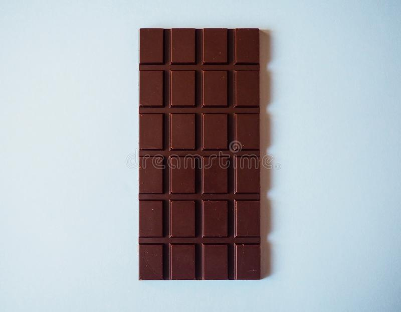Ένας φραγμός γάλακτος σοκολάτας που απομονώνεται στο μπλε υπόβαθρο από τη τοπ άποψη στοκ φωτογραφία με δικαίωμα ελεύθερης χρήσης