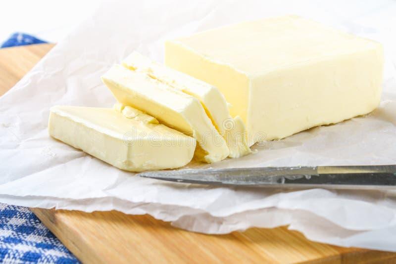 Ένας φραγμός του βουτύρου σε έναν ξύλινο πίνακα με ένα μαχαίρι, σε έναν άσπρο πίνακα Συστατικά για το μαγείρεμα στοκ φωτογραφία
