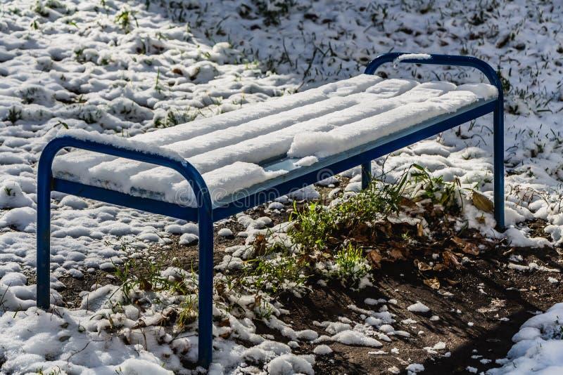 Ένας φωτεινός υγρός ξύλινος χρωματισμένος μπλε όμορφος πάγκος χρώματος με τα μπλε πόδια μετάλλων με το άσπρο χιόνι στέκεται σε μι στοκ φωτογραφία με δικαίωμα ελεύθερης χρήσης