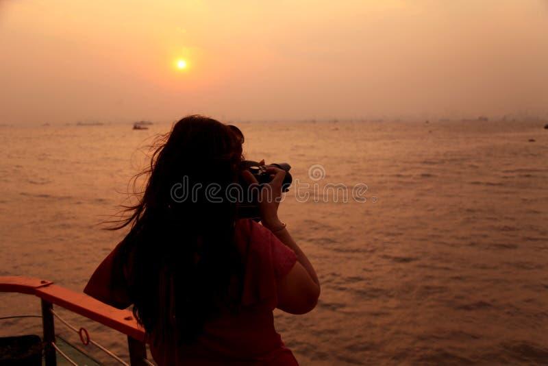 Ένας φωτογράφος που παίρνει τη φωτογραφία κατά τη διάρκεια του χρόνου του ηλιοβασιλέματος στο θαλάσσιο νερό στοκ εικόνες